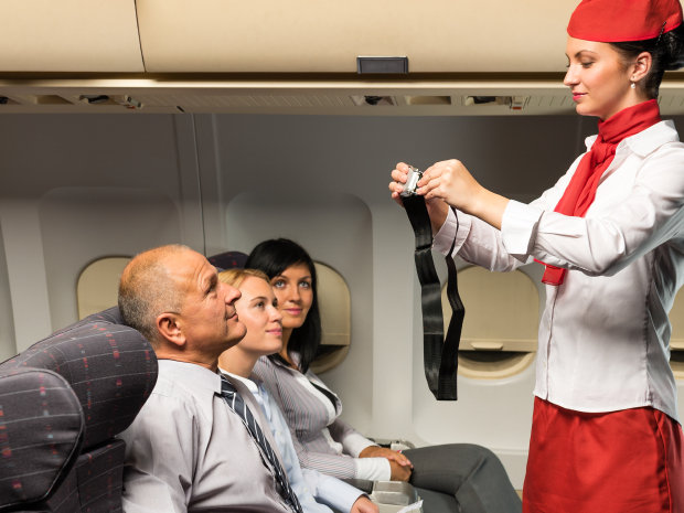 Flight attendants guide passengers before the flight starts.